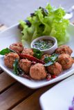 A dish of Thai style fried spicy ground pork ball served with spicy shallot sauce decorated with fried kaffir lime leaf and chilli.  royalty free stock photos