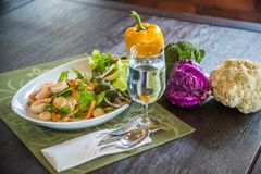 Dish of Thai style salad with cutlery, glass of water. Including broccoli, cauliflower, purple cabbage and bell pepper on wooden table in restaurant royalty free stock photo