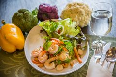 Dish of Thai style salad with cutlery, glass of water. Including broccoli, cauliflower, purple cabbage and bell pepper on wooden table in restaurant stock photos