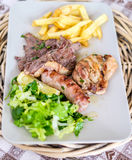 Dish with three kinds of meat, salad and chips royalty free stock photography