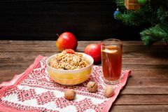 Dish of traditional Slavic treat on Christmas Eve. Christmas tree, apples, walnuts, glass of compote on a patterned tablecloth. B. Rown and blak wooden stock photos