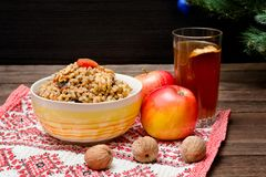 Dish of traditional Slavic treat on Christmas Eve. Christmas tree, apples, walnuts, glass of compote on a patterned tablecloth. B. Rown and blak wooden royalty free stock images