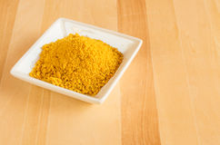 Dish of tumeric spice for use in cooking Stock Photography