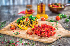Dish of twisted zucchini and sun-dried tomatoes on the board. Ro Royalty Free Stock Photos