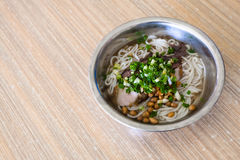 Dish with udon noodles soup with pork in eatery. Travel to China - dish with udon noodles soup with pork and guilin rice noodles on table in cheap chinese eatery Royalty Free Stock Images