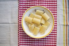 Dish of unseasoned paccheri pasta. Flat lay of unseasoned pasta paccheri on a colored tablecloth Royalty Free Stock Images