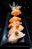 Dish of various sushi types, selective focus point with blur depth of field effect, dark atmosphere Stock Images