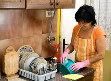 Dish washing. Woman washing dishes in the kitchen Stock Photos