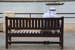 dishdasha的阿拉伯人坐一个长木凳在小河,迪拜 库存照片