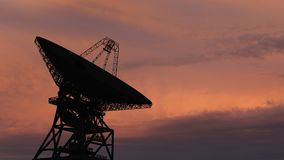Dishe por satélite que se mueve en time lapse contra un cielo de la puesta del sol metrajes