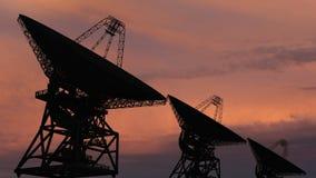 Dishe por satélite que se mueve en time lapse contra un cielo de la puesta del sol stock de ilustración