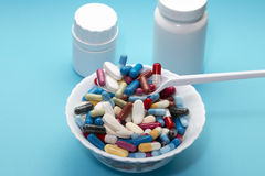 Dishes colorful pills on a plate and two bottle Royalty Free Stock Photos