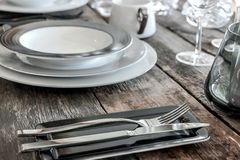 Dishes and cutlery on table Stock Photos