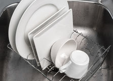 Dishes drying on a rack in the kitchen sink. White clean dishes drying on a rack in the kitchen sink royalty free stock photos