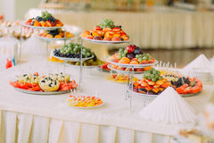 Dishes with fruits on catering banquet table decorated by white napkins Stock Images