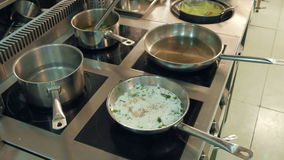 Dishes in frying pans being cooked on a stove while chef regulating temperature stock video footage