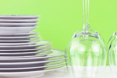 Dishes and Glasses. Plates and glasses against a green green background Royalty Free Stock Photo