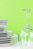 Dishes and Glasses. Plates and glasses against a green green background Royalty Free Stock Image
