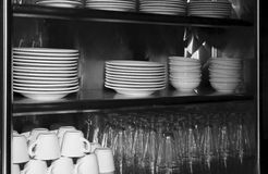 Dishes And Glasses On A Diner Shelf. Ceramic dishes and glasses displayed on a family diner style shelf Stock Photography