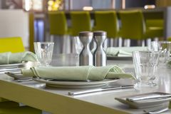 Dishes and glasses with napkin on dining table. Dishes and glasses with napkin and salt and pepper on dining table Stock Image