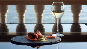 Dishes at the gourmet restaurant. Close-up. Cutlet from rabbit meat with a garnish of green buckwheat. A glass of white. Wine. Seaside restaurant with sea view stock footage