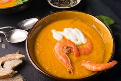 2 dishes of orange pumpkin soup on a black table. Three red shrimps decorate the soup. stock photos