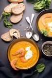 2 dishes of orange pumpkin soup on a black table. Three red shrimps decorate the soup. stock image