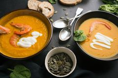 2 dishes of orange pumpkin soup on a black table. Three red shrimps decorate the soup. royalty free stock image