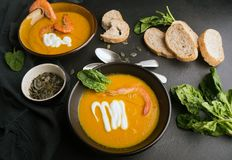 2 dishes of orange pumpkin soup on a black table. Three red shrimps decorate the soup. royalty free stock images