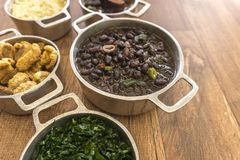 Dishes that are part of the traditional feijoada, typical Brazilian food. Black beans, cabbage, crackers, white rice, dried meat, paio stock images