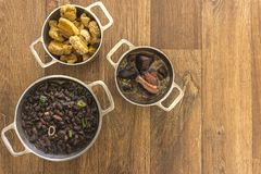 Dishes that are part of the traditional feijoada, typical Brazilian food. Black beans, cabbage, crackers, white rice, dried meat, paio stock photo