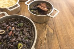 Dishes that are part of the traditional feijoada, typical Brazilian food. Black beans, cabbage, crackers, white rice, dried meat, paio stock image