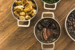 Dishes that are part of the traditional feijoada, typical Brazilian food. Black beans, cabbage, crackers, white rice, dried meat, paio stock photos