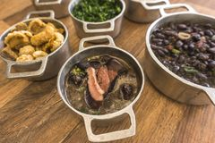 Dishes that are part of the traditional feijoada, typical Brazilian food. Black beans, cabbage, crackers, white rice, dried meat, paio royalty free stock image