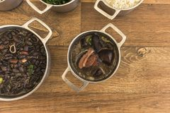 Dishes that are part of the traditional feijoada, typical Brazilian food. Black beans, cabbage, crackers, white rice, dried meat, paio royalty free stock photos