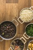 Dishes that are part of the traditional feijoada, typical Brazilian food. Black beans, cabbage, crackers, white rice, dried meat, paio royalty free stock photo