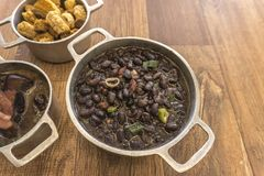 Dishes that are part of the traditional feijoada, typical Brazilian food. Black beans, cabbage, crackers, white rice, dried meat, paio royalty free stock photography