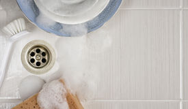 Dishes in the sink with a brush and sponge. Ceramic in the sink with a brush and sponge Royalty Free Stock Image