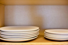Dishes stacked in the cabinet. Porcelain white dishes stacked in the cabinet Royalty Free Stock Images