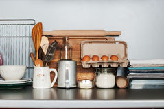 Dishes, Tableware and Products stand on a Kitchen Table Stock Photo
