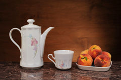 Dishes for tea and fresh peaches Royalty Free Stock Photo
