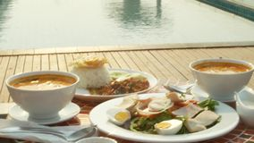 Dishes of Thai cuisine. 4k. table by the pool. Thai traditional lunch by the pool stock video