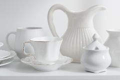 dishes and vases on white wooden shelf Royalty Free Stock Image