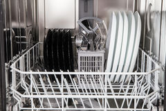 Dishes after washing in modern dishwasher machine Stock Image