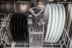 Dishes after washing in modern dishwasher machine Stock Photos
