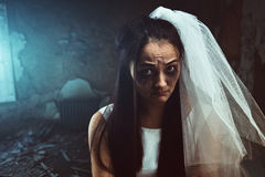 Disheveled bride with tear stained face. In white veil, abandoned house interior on background Stock Photos