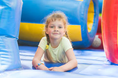 Disheveled five year old girl is playing on big inflatable trampoline Stock Photo