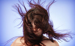 Disheveled hair, covered his face. Blue background Royalty Free Stock Photo