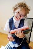 Disheveled mały uczeń trzyma stertę podręczniki i uśmiechy zdjęcie royalty free
