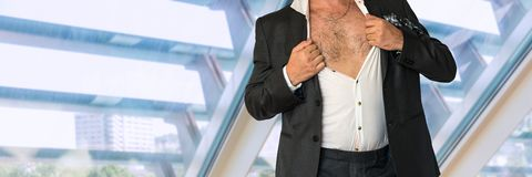 Disheveled man in business suit with an unbuttoned shirt. In office Royalty Free Stock Image
